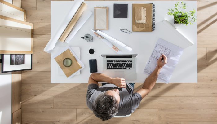 architect sitting at desk and working on his laptop, there is blueprints and model house on his table, the sun casts graphics shadows on the wood floor